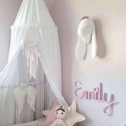 Biały baldachim dla dziewczynki z pomponikami nad łóżeczko